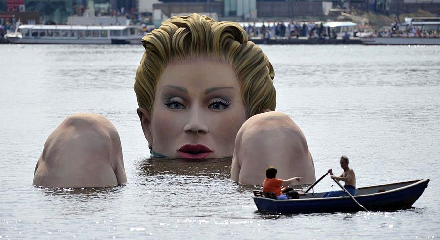 Из воды торчит только голова блондинки и голые колени.