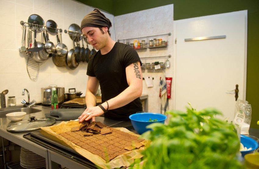 """Совладелец первого европейского ресторана """"Каменный век """" в Берлине - Борис Лейте-Poco, готовит еду на кухне ресторана"""
