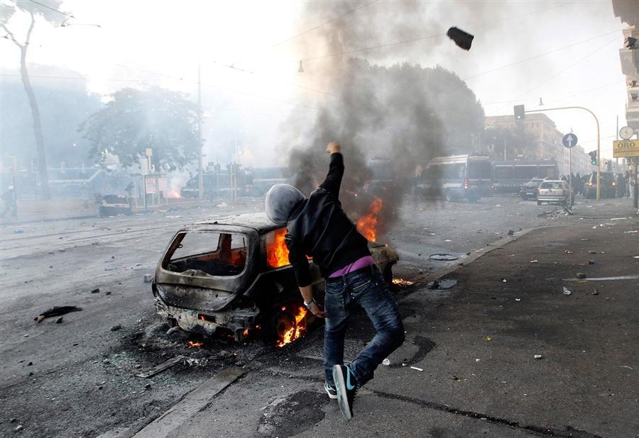Демонстрант бросает камень в полицию во время акции протеста в Риме
