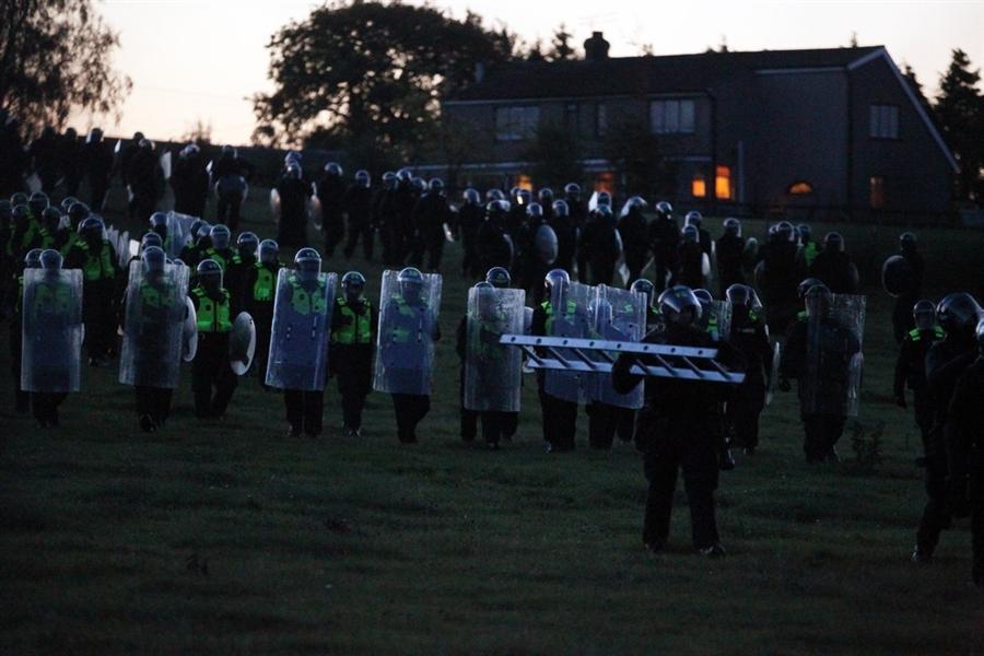 Отряд полиции в защитном снаряжении идет через поле в лагерь