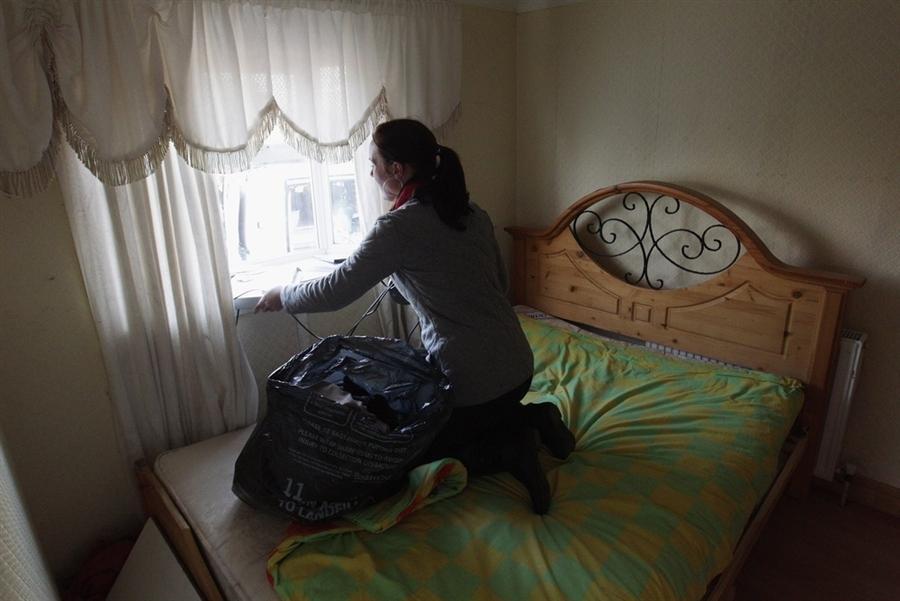 Жительница одного из домов на колесах, очищает свой караван перед выселением