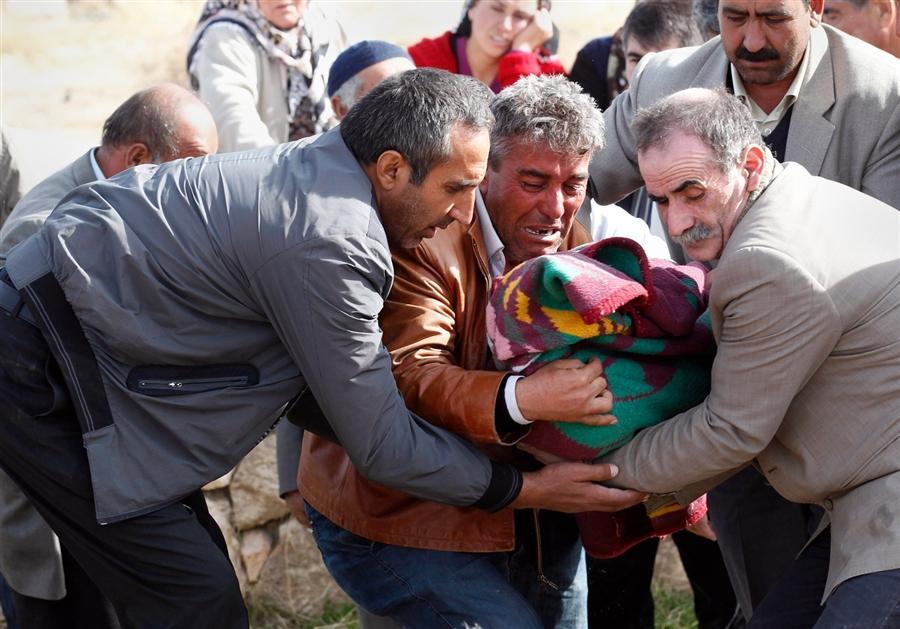 Первые похороны - отец несет на кладбище свою дочь, Турция, 24 октября