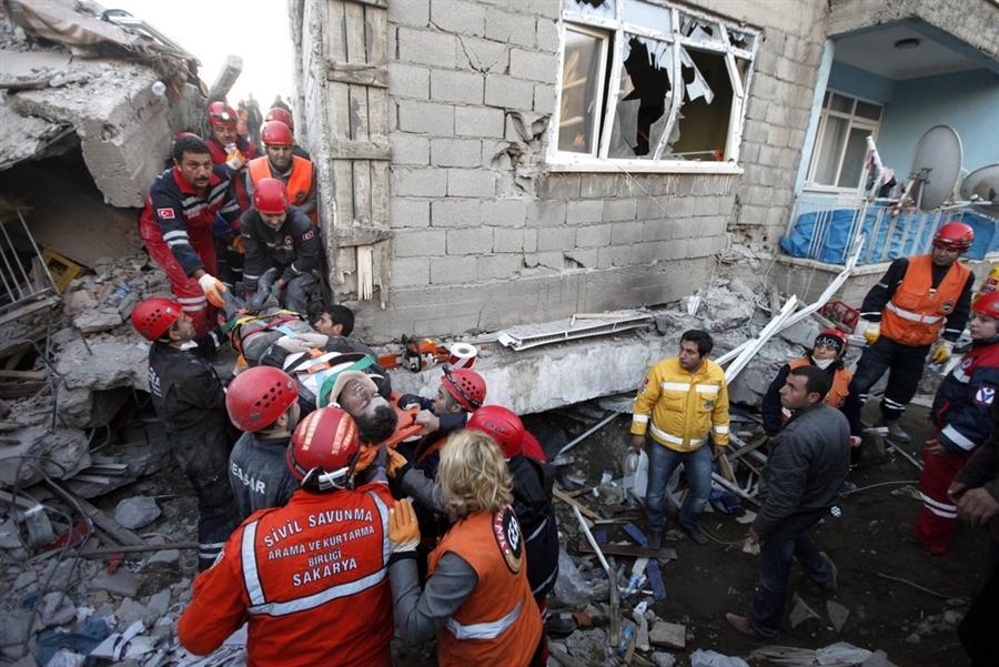 Спасатели выносят раненого из под обломков рухнувшего дома в городе Erci?, Турция, 24 октября