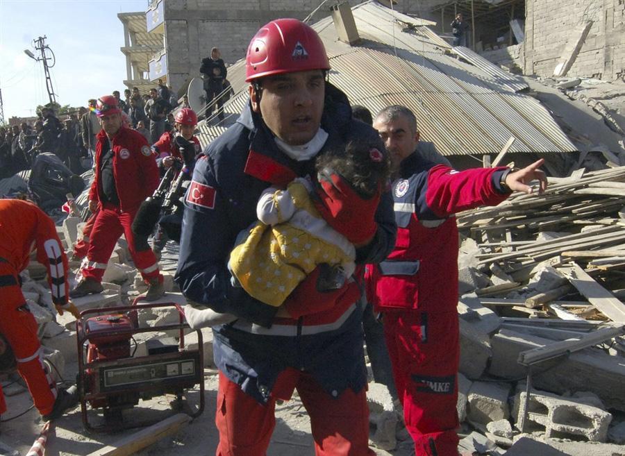 Спасатель бежит к карете Скорой помощи с маленькой девочкой на руках, город Erci?, Турция,  24 октября