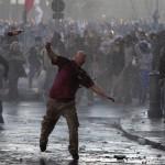 Протестующие бросают в полицейских бутылки, недалеко от Коллизия