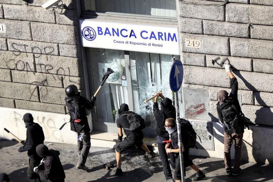 Демонстранты бьют стекла дверей одного из банков Рима