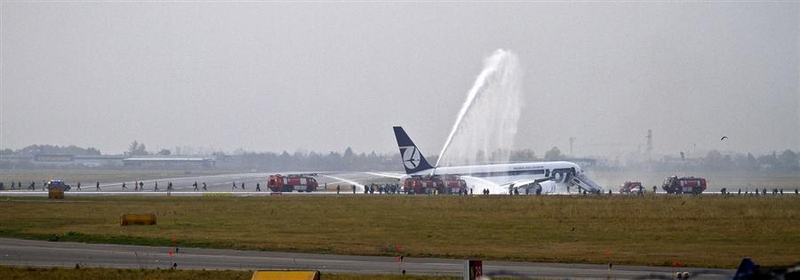 Пожарные машины обливают самолет от возгорания после приземления