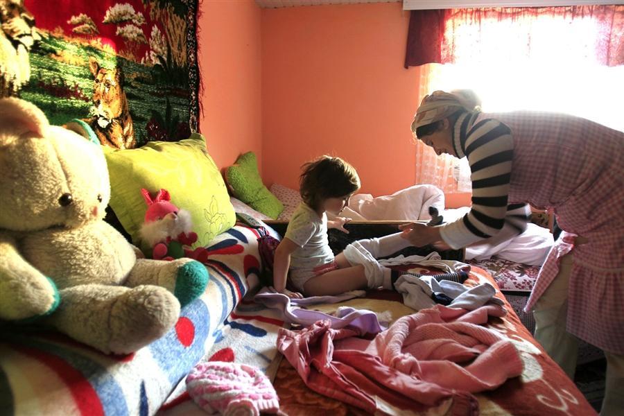 Сельская жительница Женовева, 35-ти лет, собирает свою дочь Стефанию в детский сад в Hreasca
