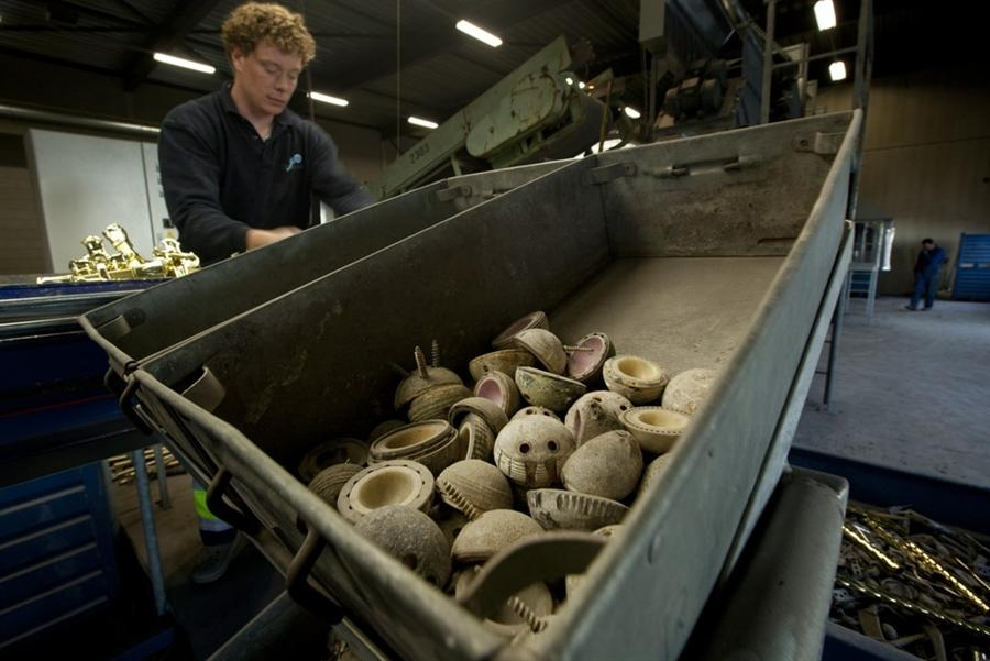 Сотрудник  OrthoMetals отделяет украшения для гроба от человеческих имплантантов