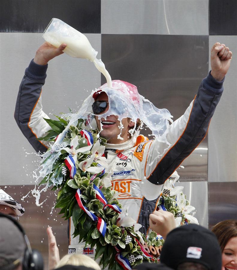 Дэн Уэлдон из Англии льет молоко на себя после победы на 100-летие Индианаполис 500 в мае месяце