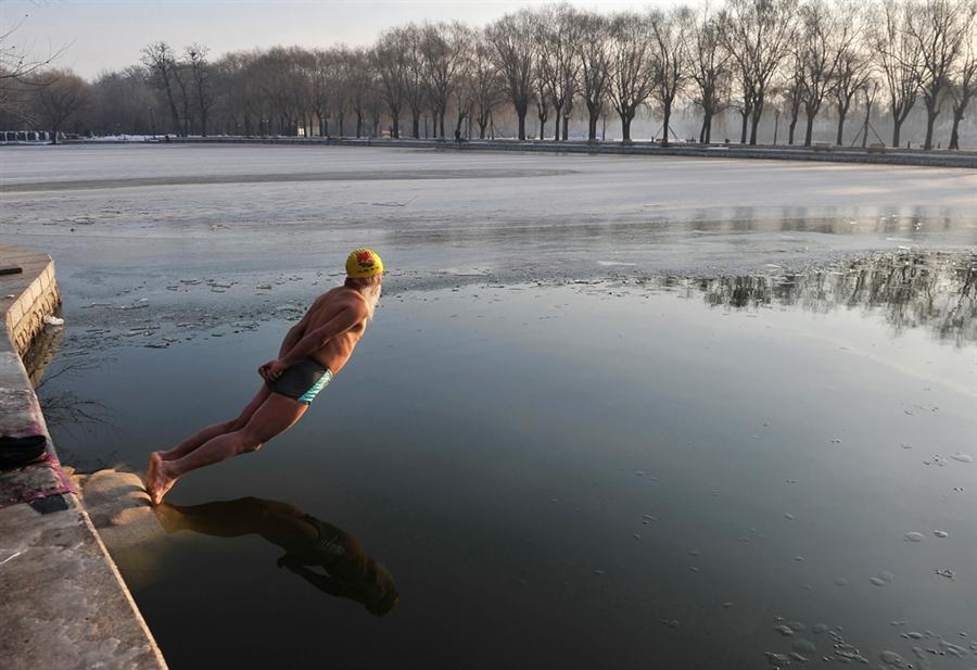Пожилой китаец укрепляет иммунную систему, ныряя в ледяную воду озера Beiling, 2 декабря