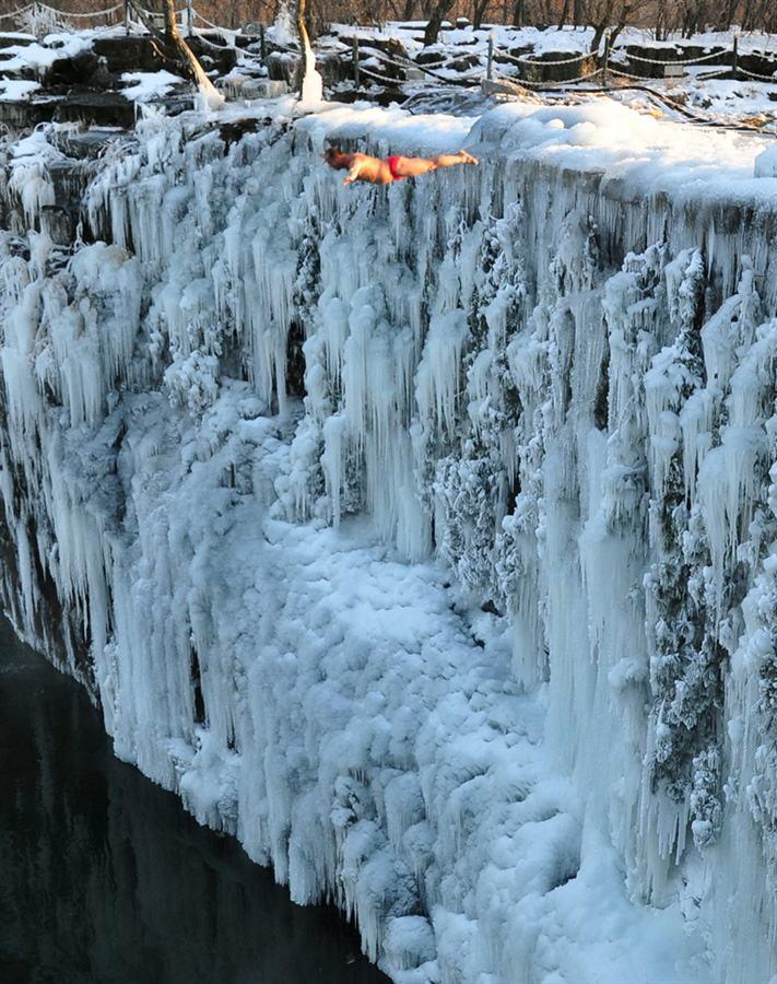 Китаец прыгает с замерзшего водопада в озеро в провинции Хэйлунцзян, 20 декабря