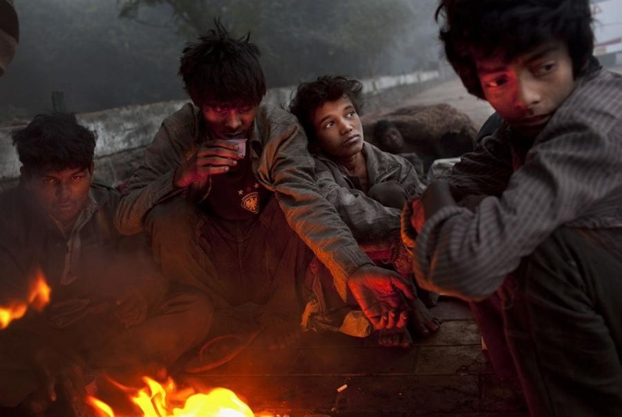 Бездомная индийская молодежь греется у костра в Нью-Дели, 20 декабря