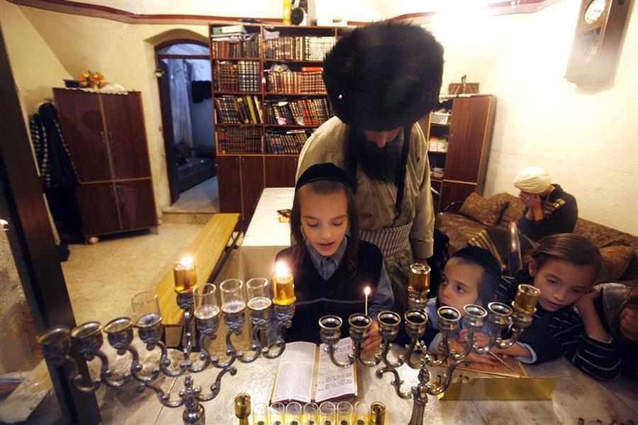 Ультра-ортодоксальные еврейские семьи зажигают масляные свечи в Иерусалиме