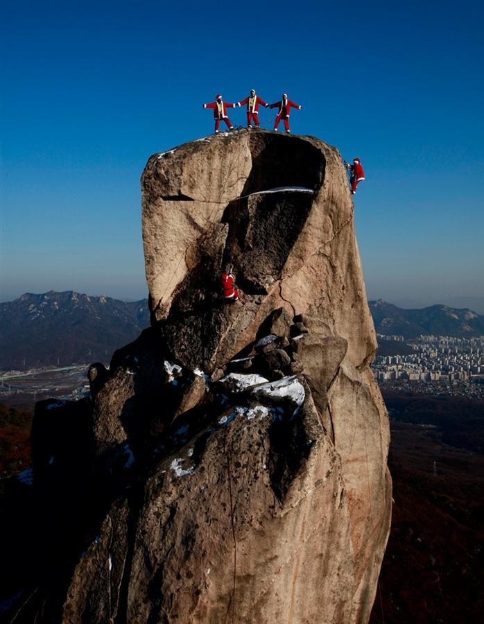 Санта Клаусы - альпинисты недалеко от Сеула в Южной Корее