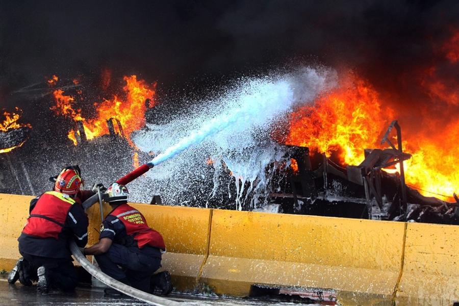 Пожарные тушат бензовоз, который перевернулся и взорвался 29 декабря в  Каракасе, 14 человек погибли и 16 серьезно ранены