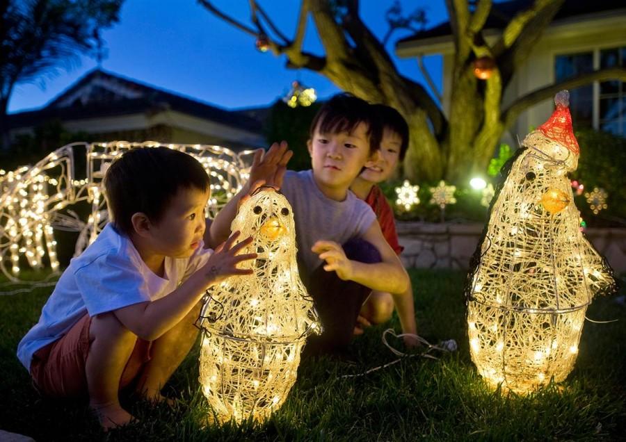 Дети радуются включению рождественских украшений у дома в Калифорнии