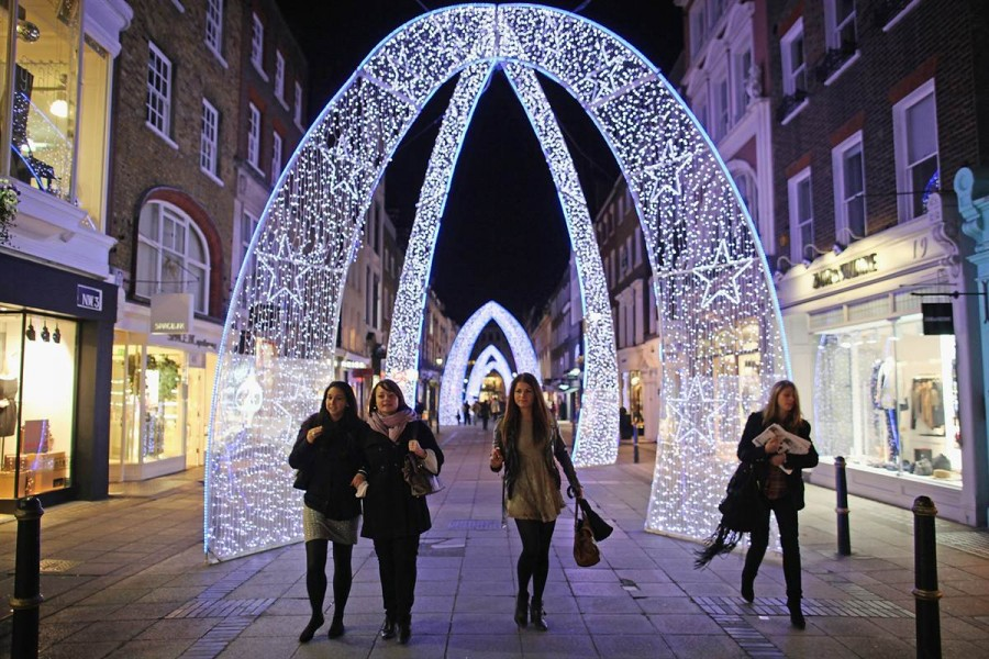 Лондонцы ходят за рождественскими покупками под освещенными арками-гирляндами