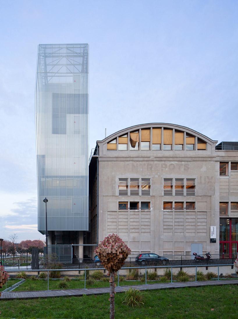 Тонкий металлический фасад и мягкая подсветка скрашивают большие размеры здания