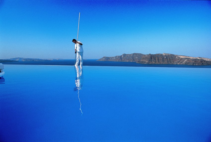 Чистка бассейна на краю пропасти, отель  Katikies на греческом острове Санторини