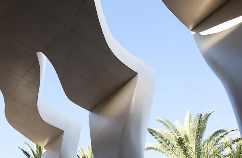 Монолитная форма крыши и столбцов плавно соединяется со стеклянным фасадом