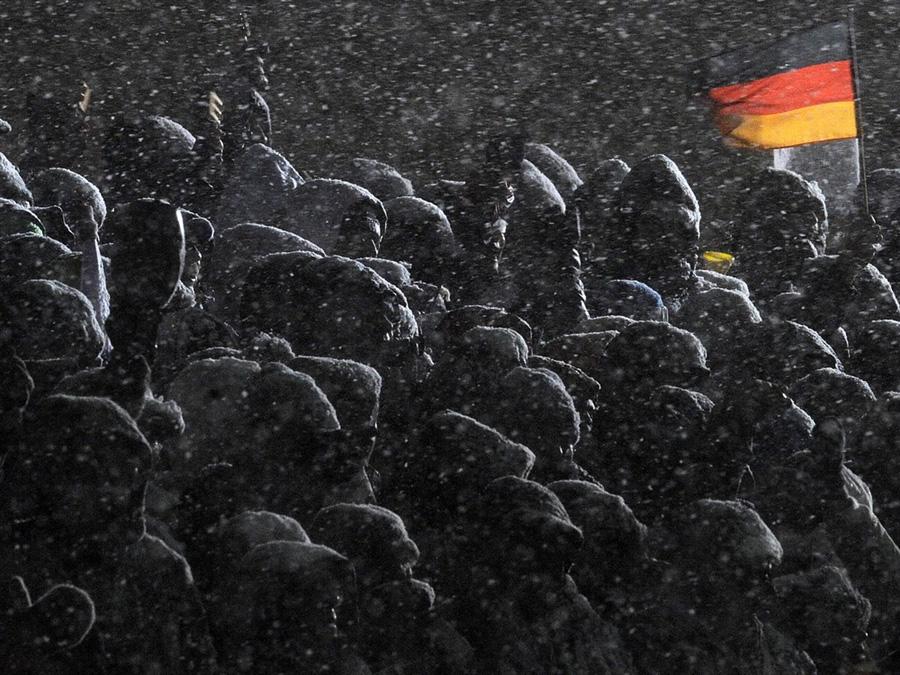 Зрители наблюдают за мужской биатлонной эстафетой 4 х 7,5 км поди сильнейшим снегопадом в Оберхофе на Кубке Мира