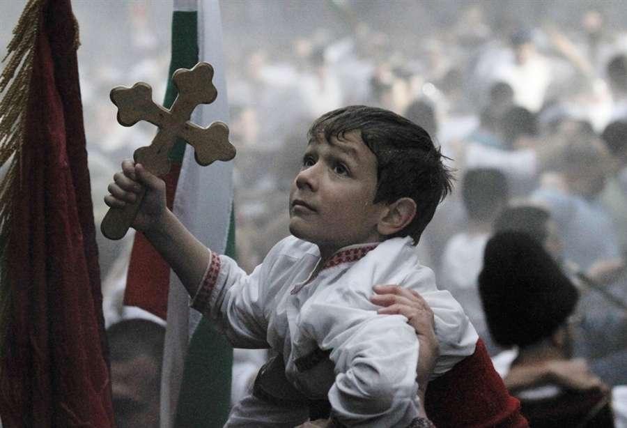 Ребенок держит крест, сидя на плечах своего отца на реке Тунджа, празднование Крещения в болгарском городе Калофер