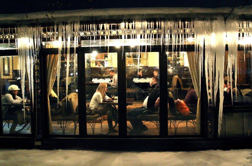Люди сидят в ресторане Сербии, на здании огромные сосульки