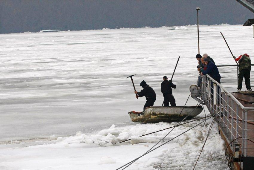 Люди пытаются долбить лед вокруг плавучего ресторана в Белграде