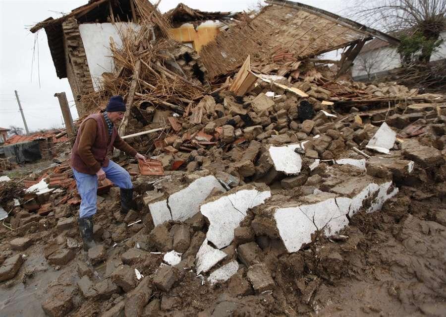 Человек перебирает остатки своего дома в поселке Бисер