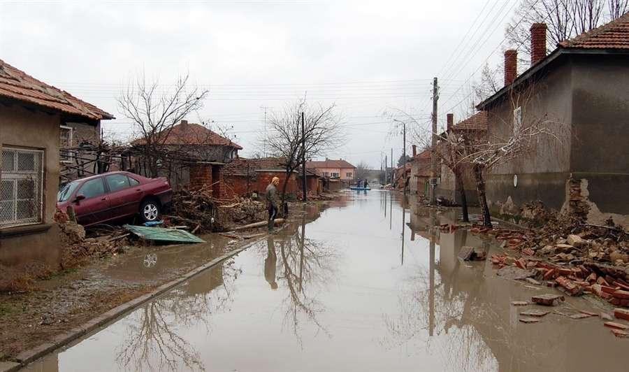 Мужчина стоит рядом с домом на затопленной улице