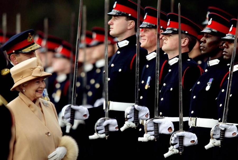 Принц Гарри широко улыбается, когда его бабушка королева Елизавета рассматривает военных во время парада в Королевской военной академии в Сандхерсте в графстве Суррей, в апреле 2006 года
