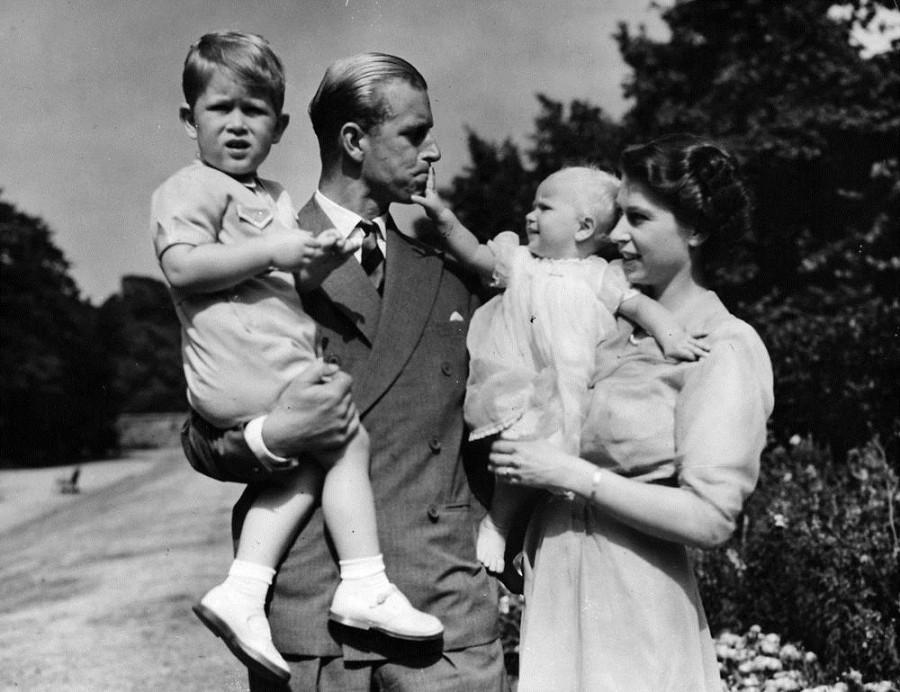 Принцесса Елизавета стоит со своим мужем, принцем Филиппом, и их детьми принцем Чарльзом и принцессой Анной в Кларенс-хаус, лондонской резиденции королевской четы в августе 1951 года