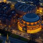 Огни Royal Albert Hall излучают золотой свет, подчеркивая круглую форму здания