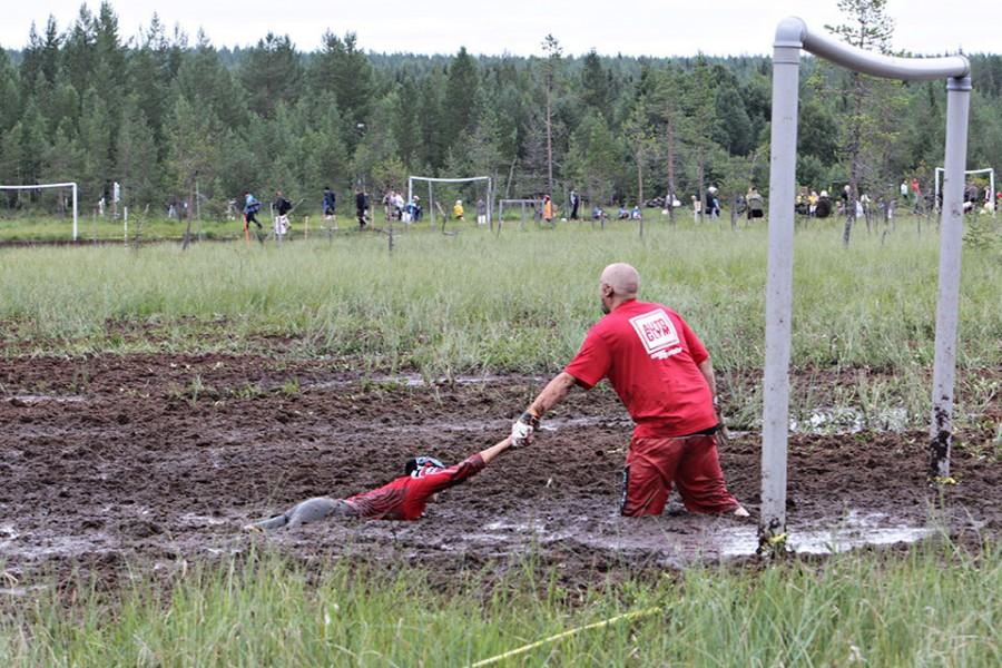 Вратарь помогает игроку команды, застрявшему в грязи
