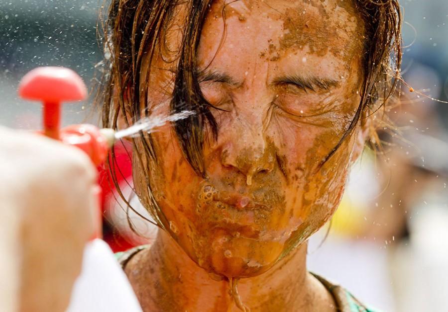 Игрок смывает грязь с лица в Swamp Soccer в Китае