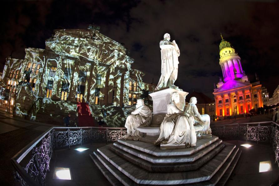 """Статуя немецкого поэта Фридриха Шиллера, Концертный зал (слева) и Французский собор в Берлине во время ежегодного """"Фестиваля света"""", 10 октября 2012, фото Odd Andersen / AFP / Getty Images"""