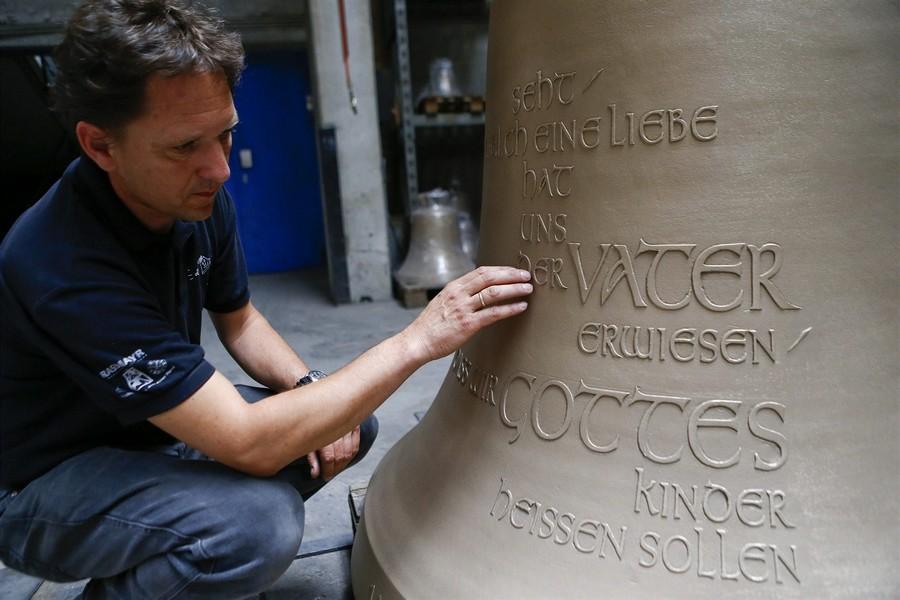 Владелец фирмы Петр Грассмайэр у своего колокола. На колоколе высечен третий стих 1 главы из Библии Иоанна.