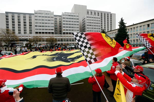Команда Феррари и фанаты Шумахера возле больницы Гренобля, где находится гонщик