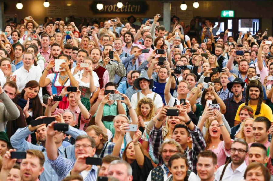 Visitors watch the opening ceremony for the 182nd Oktoberfest in Munich, Germany, September 19, 2015. Millions of beer drinkers from around the world will come to the Bavarian capital over the next two weeks for Oktoberfest, which starts today and runs until October 4, 2015. REUTERS/Michael Dalder