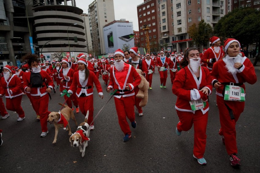 MADRID, SPAIN - DECEMBER 12: Participants run along Castellana Street during the fourth edition of the yearly Santa Claus 'Papa Noel' race on December 12, 2015 in Madrid, Spain. Around ten thousand adults dressed as Santa Claus and children dressed as elves turned out to take part in the 5.5 kilometres, breaking the world record for the race with the most competitors dressed as Santa Claus. Part of the earnings will be donated to the Foundation for Multiple Sclerosis of Madrid. (Photo by Pablo Blazquez Dominguez/Getty Images)